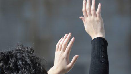 mani in alto